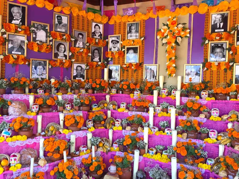 Pictures of deceased surrounded by marigolds and candles.