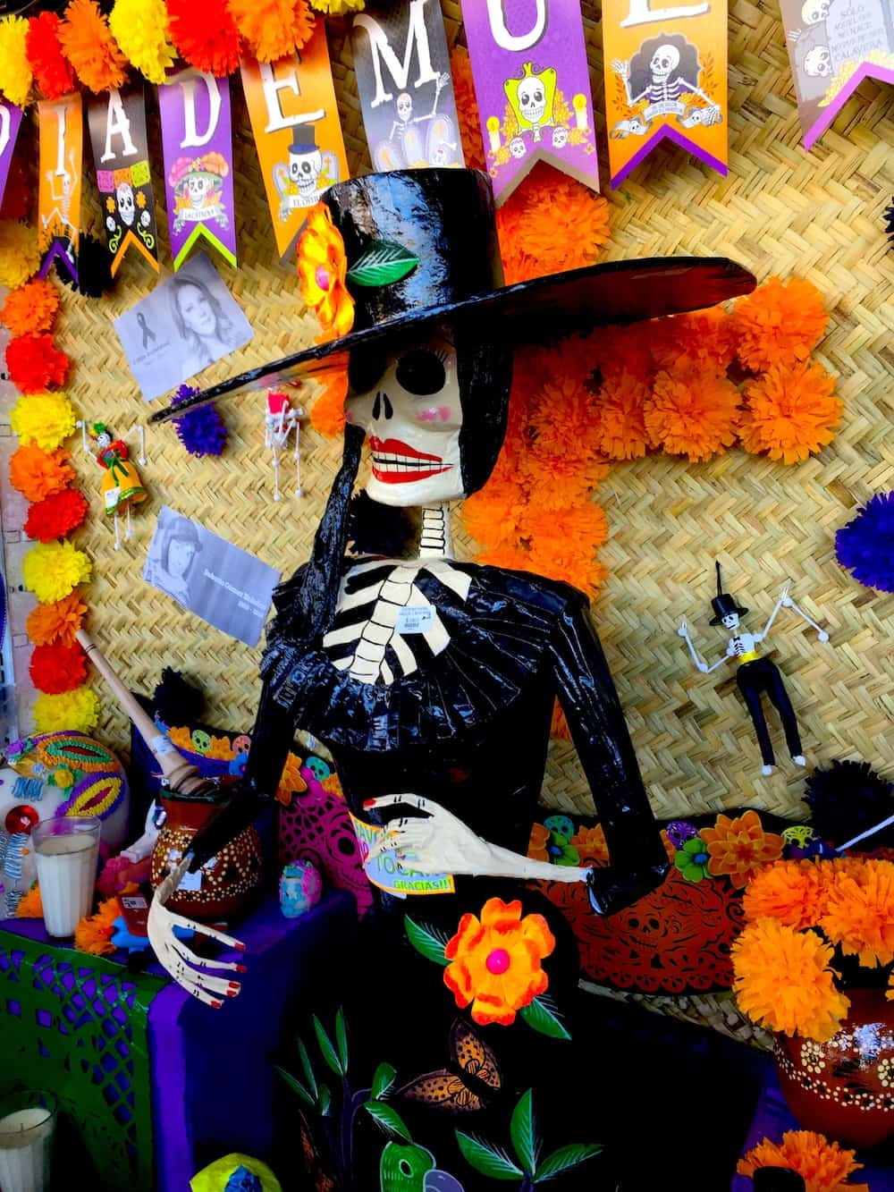 La Catrina in a black hat surrounded by marigold flowers.