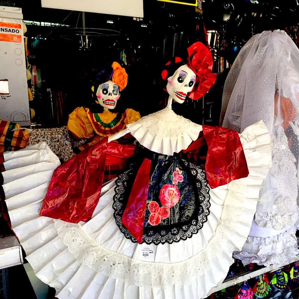 Two La Catrina dolls dressed in decorative Mexican dresses.