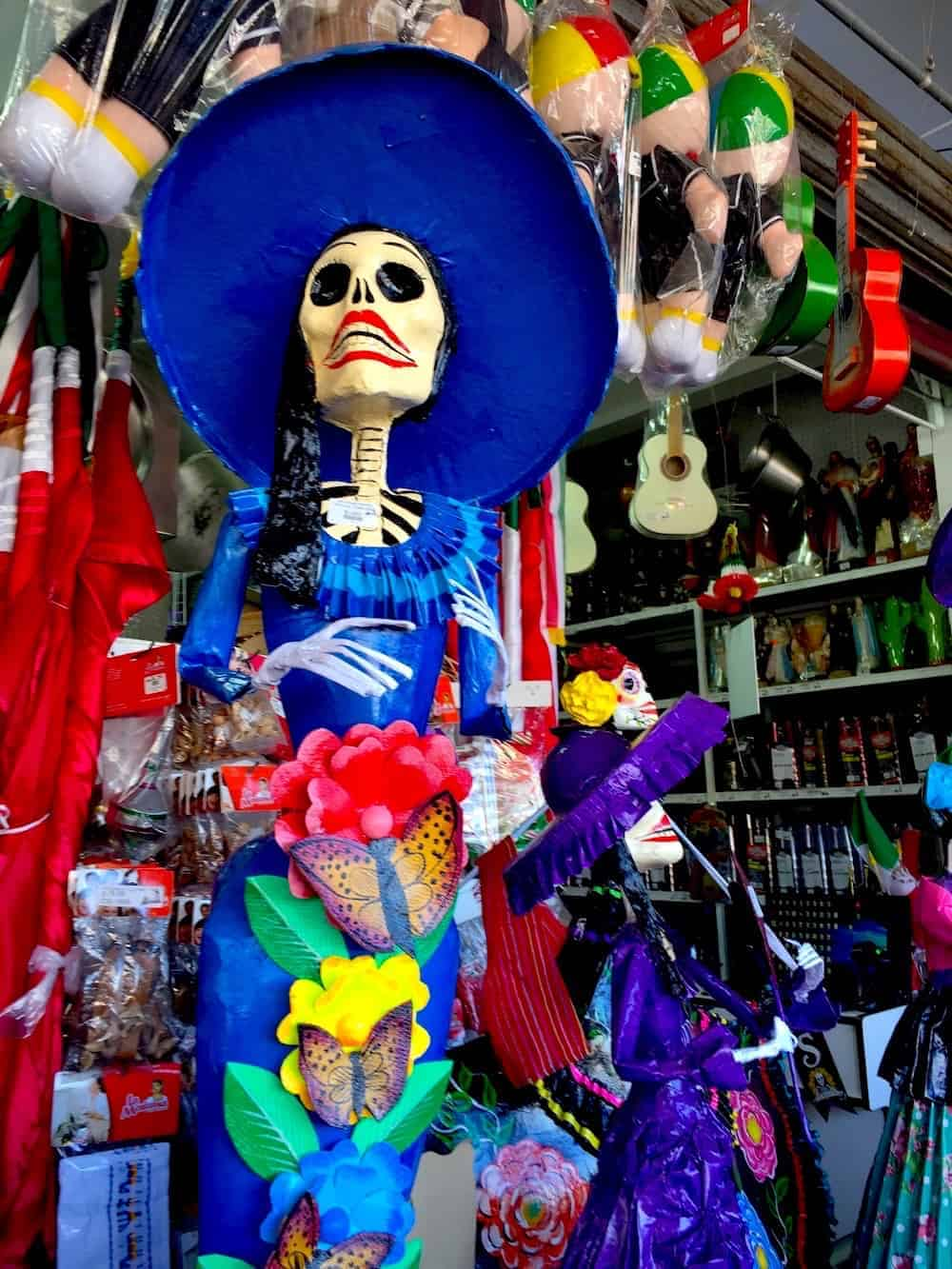 A stature of La Catrina wearing a blue hat and a blue dress.
