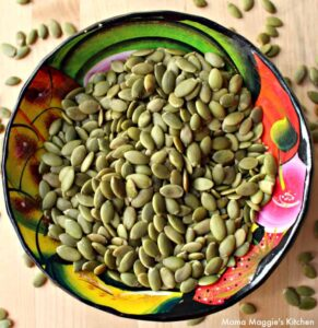 Pepitas pumpkin seeds in a decorative and colorful bowl.