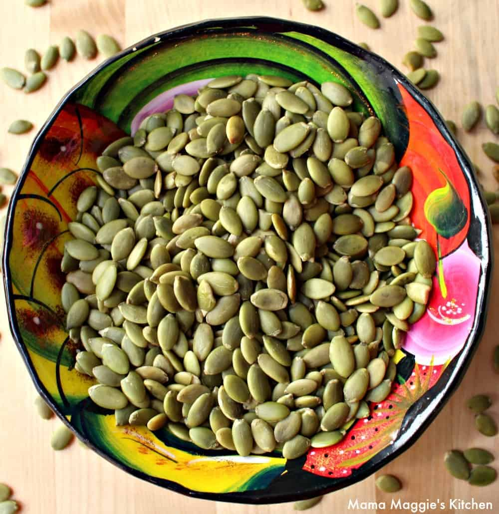 Mexican pumpkin seeds in a decorative and colorful bowl.