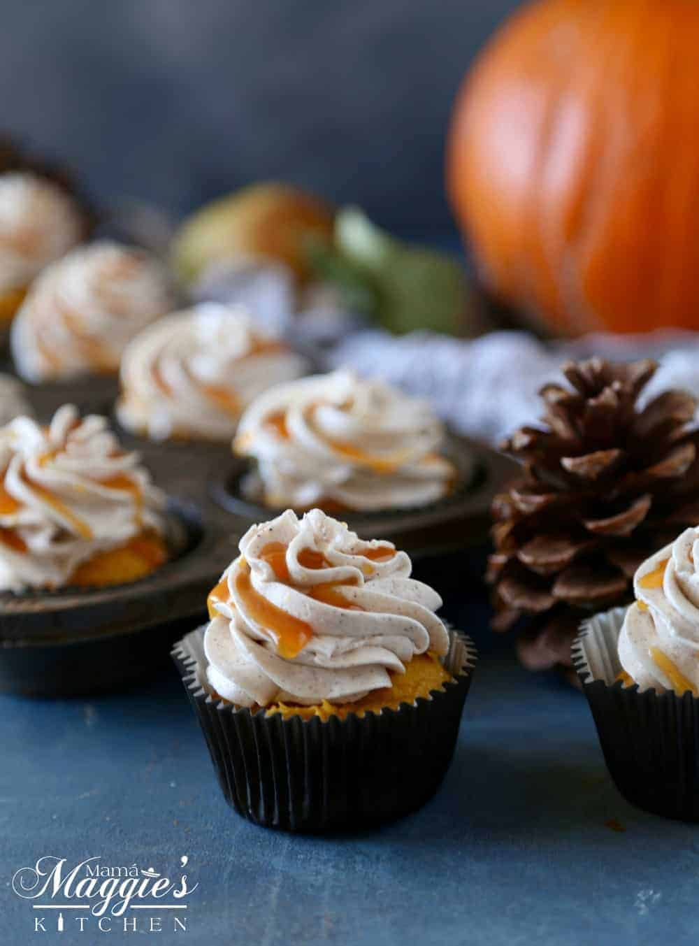 Pumpkin cupcakes topped with frosting and drizzled with cajeta next to a pine cone and an orange pumpkin.