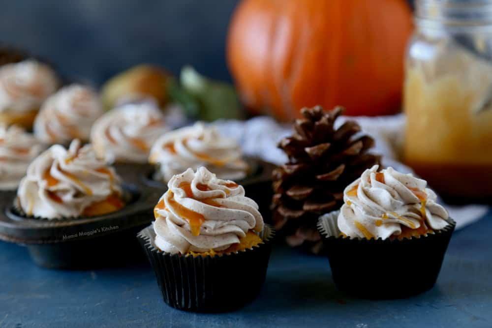 Pumpkin cupcakes next to a pine cone and jar of cajeta.