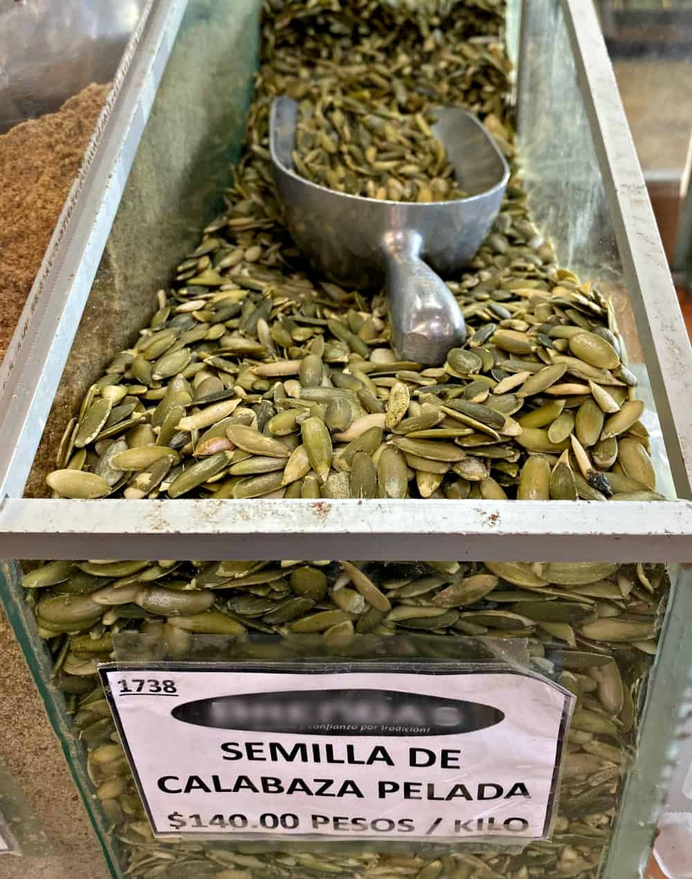 Mexican pumpkin seeds in a bin with a spoon inside.