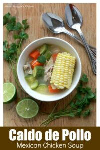 Mexican Chicken Soup in a white bowl surrounded by lime and cilantro leaves.