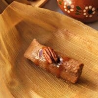 A tamal sitting on top of a corn husk drizzled with cajeta sauce and topped with a pecan next to a decorative clay mug.