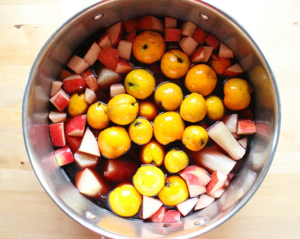 A picture of a large stock pot with fruit.