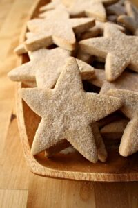 Star-shaped hojarascas cookies on a wooden platter.