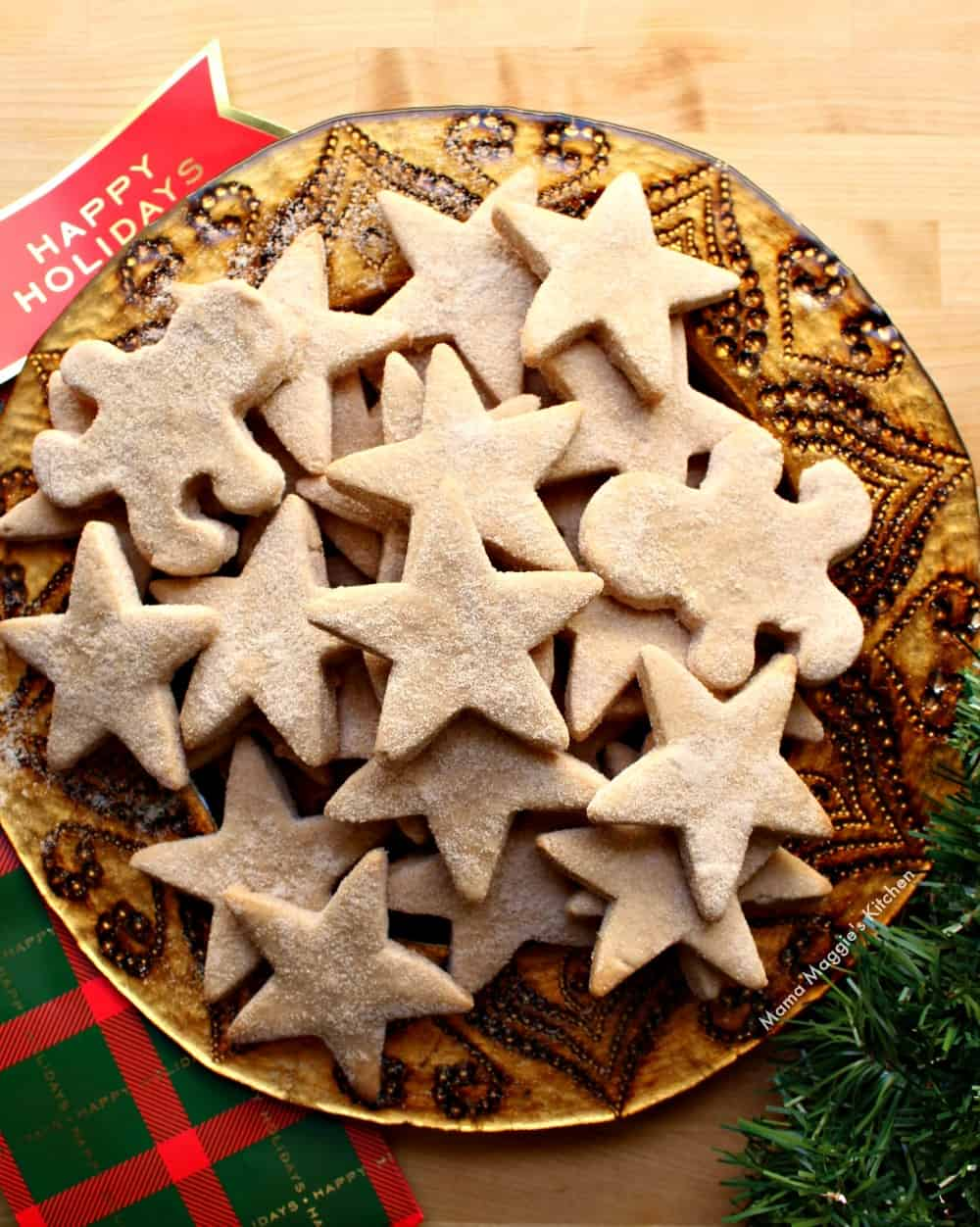 Mexican shortbread cookies on a gold, round plate next to Christmas decorations.