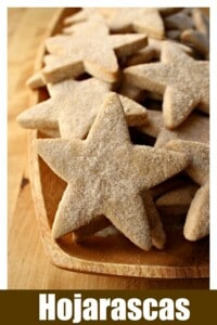 Star-shaped hojarascas cookies on a wooden platter.