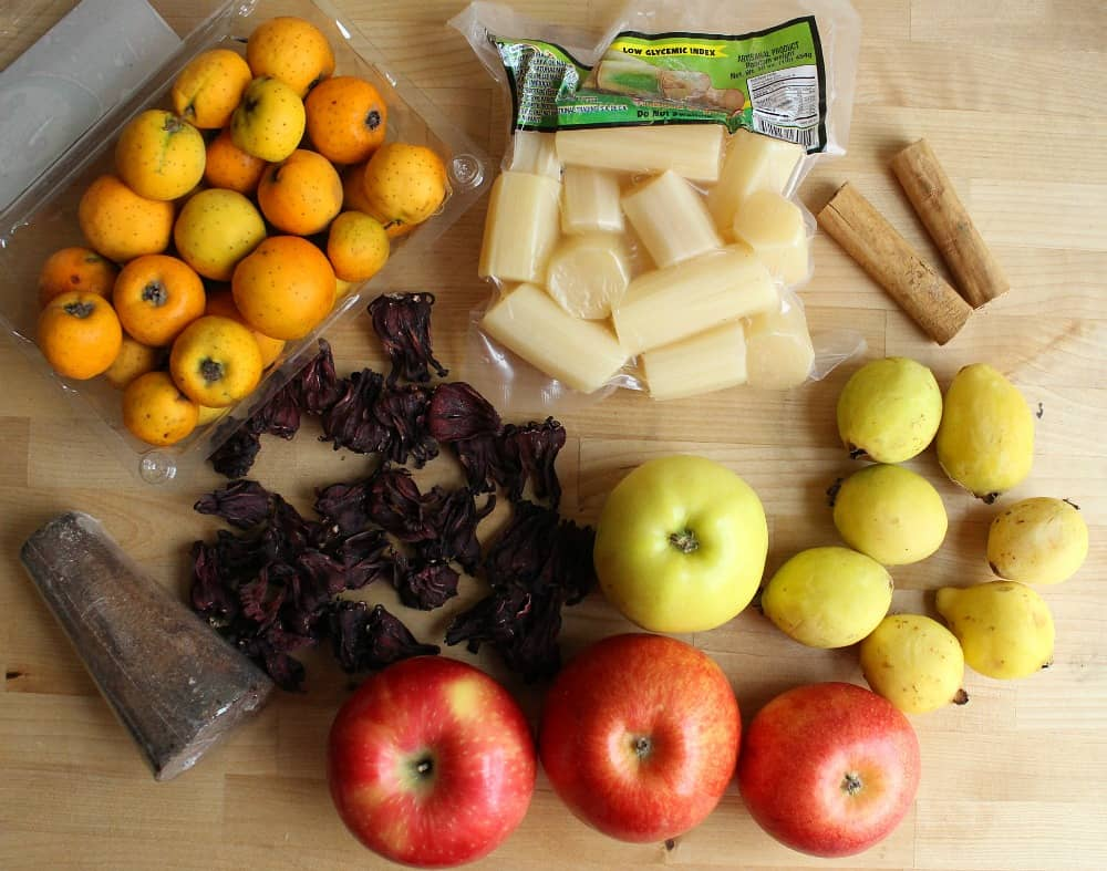 Ingredients for Ponche Navideno on a wooden table.