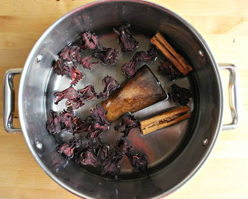 Cinnamon, piloncillo, and hibiscus leaves in a pot with water.
