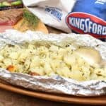A picture of potatoes wrapped in a foil packet next to a package of Kingsford charcoal.