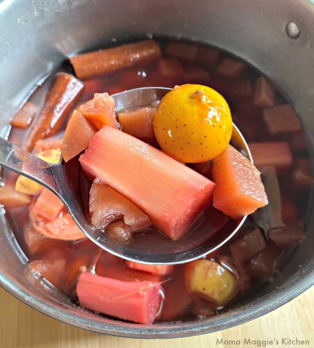 A ladle holding the fruit from the punch over a large stock pot.
