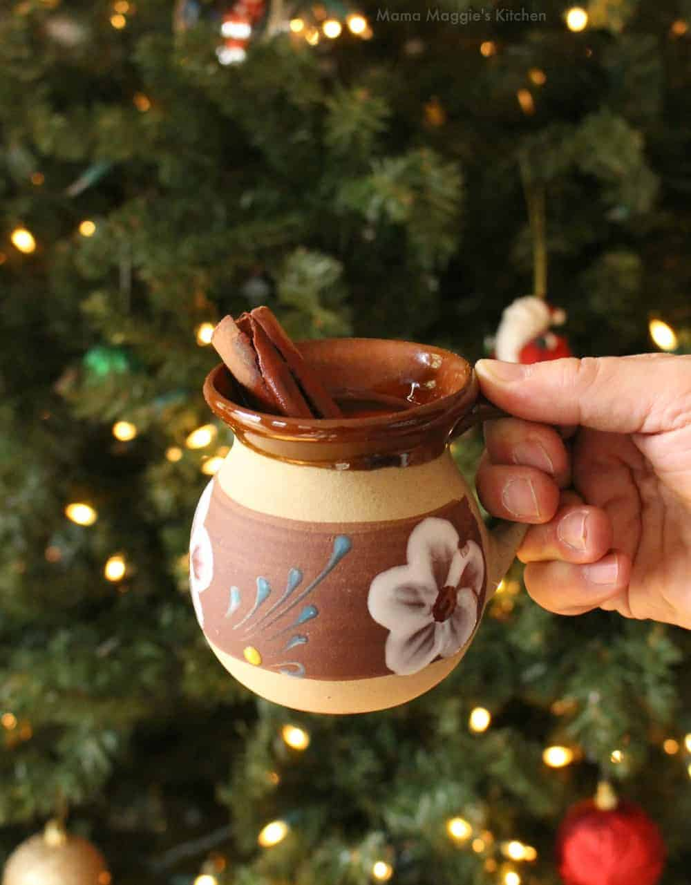Hand holding a decorative clay mug with Ponche Navideno next to a Christmas tree.