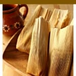 Tamales de Cajeta on a wooden platter next to a decorative mug.
