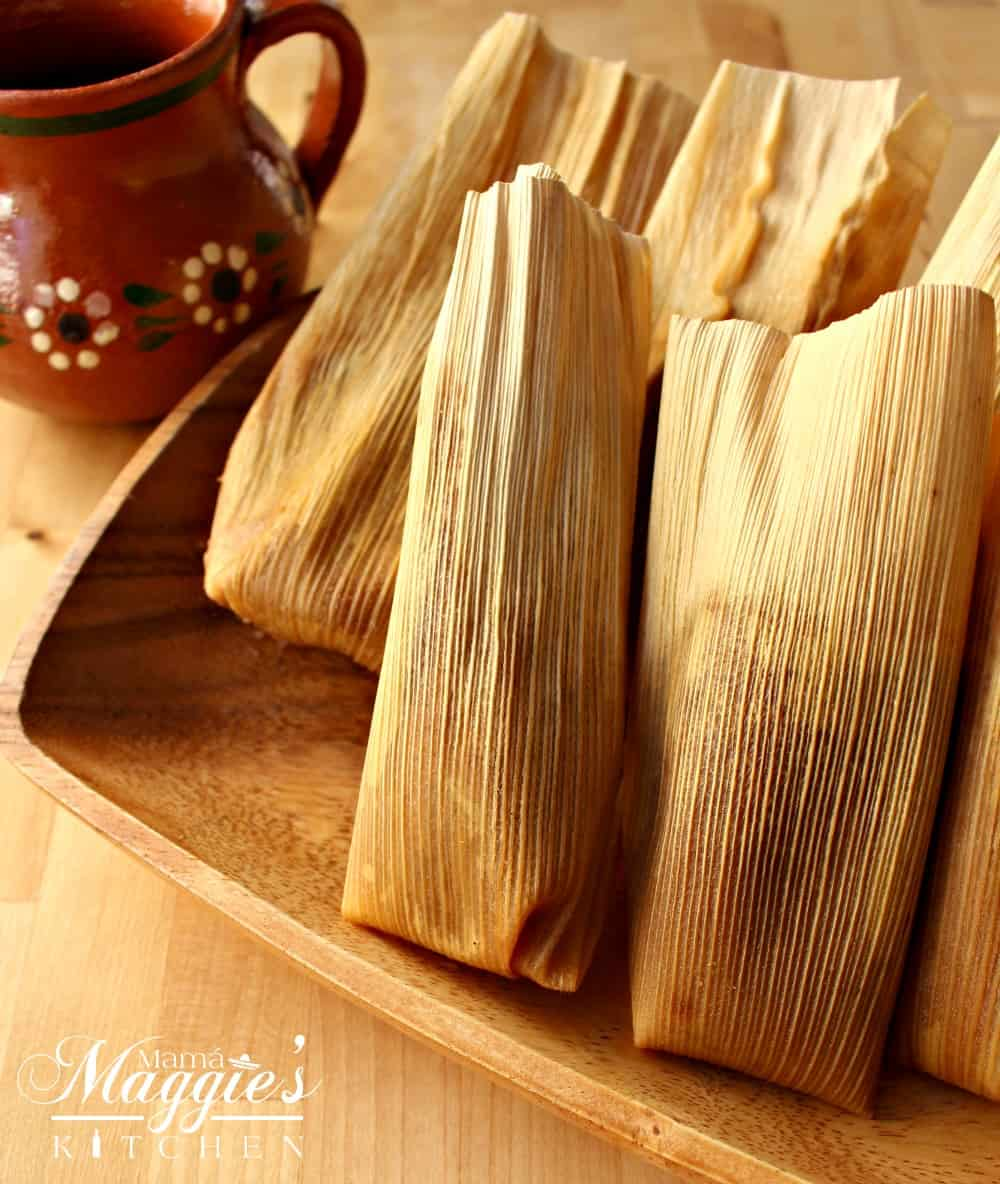 Tamales on a wooden serving dish next to a decorative Mexican clay cup.
