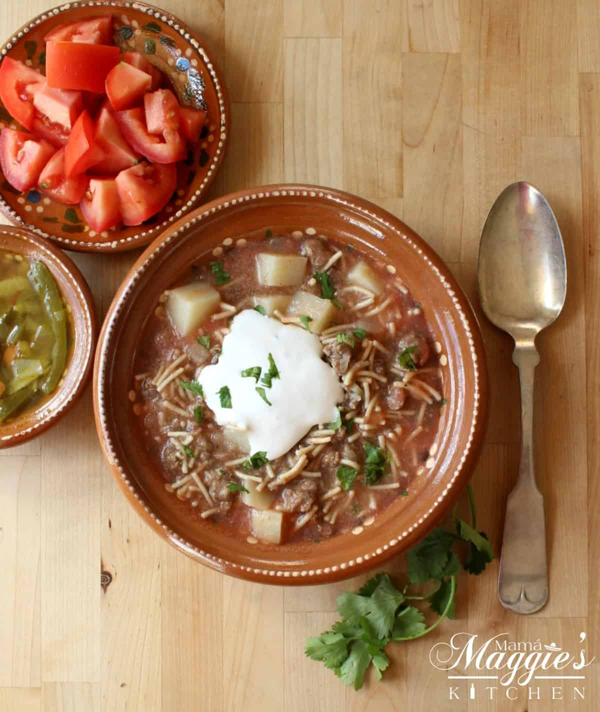 A decorative clay bowl of Fideo con Carne topped with sour cream next to a spoon and tomatoes.