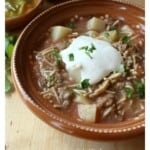 Fideo con Carne in a decorative clay bowl topped with sour cream and chopped cilantro.