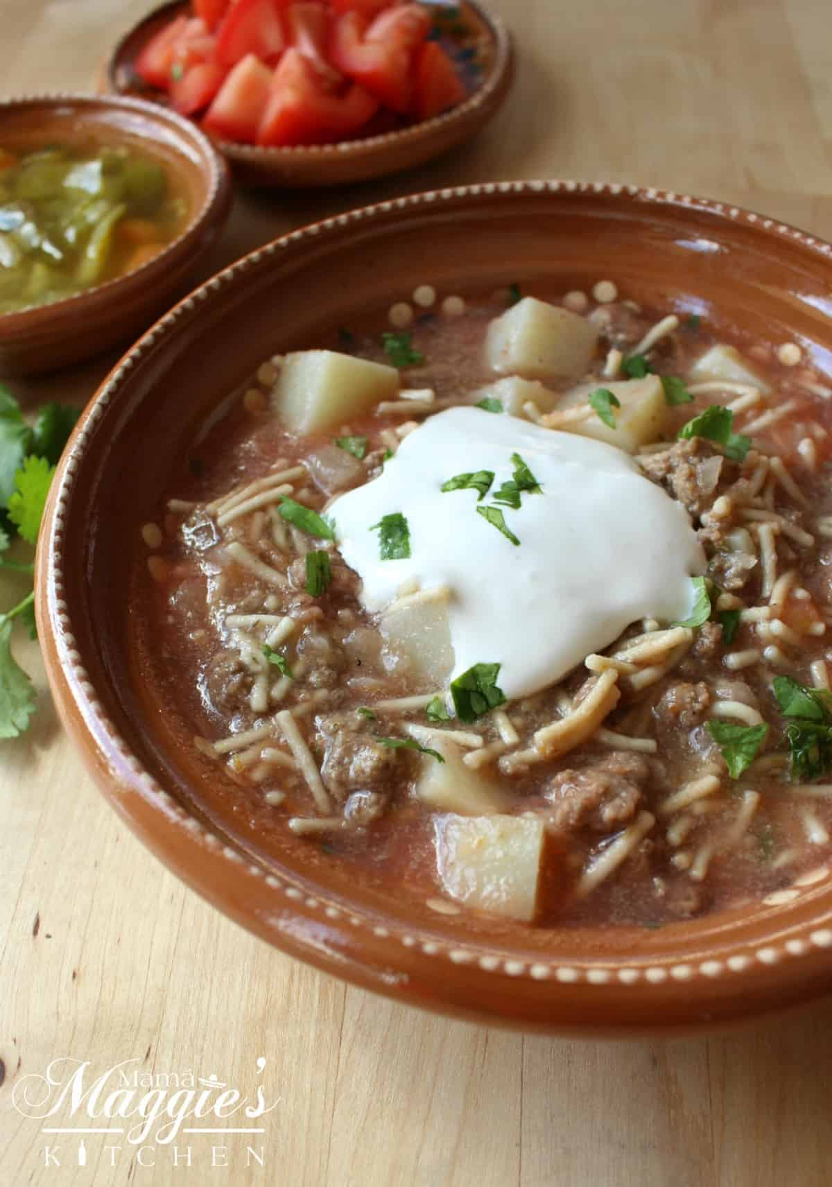 Fideo con Carne in a clay bowl topped with sour cream and chopped cilantro.