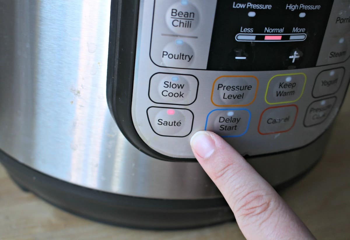 A finger pointing to the saute button on the instant pot.