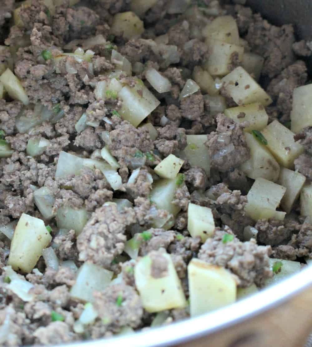 Cooked ground beef and potatoes in a stock pot.