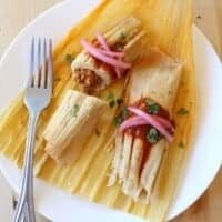 Two turkey pibil tamales on a corn husk topped with pickled red onions and chopped cilantro.