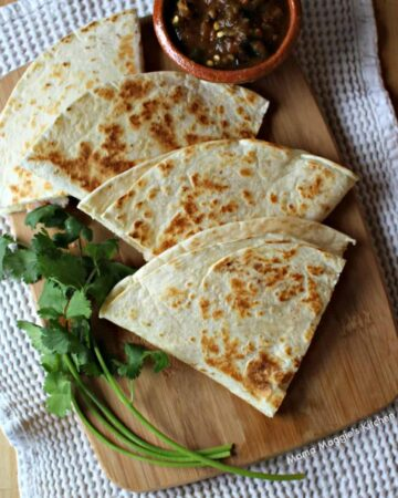 Shrimp Poblano Quesadillas on a wooden cutting board surrounded by cilantro leaves and salsa.