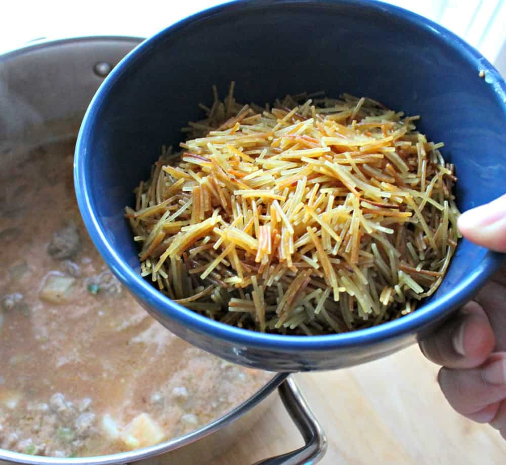 Hand holding a blue bowl full of toasted fideo noodles.