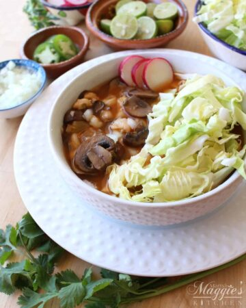 Vegan pozole in a white bowl topped with cabbage and sliced radishes surrounded by more toppings.