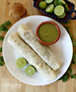 Two Durango Burritos on a white plate next to salsa verde and lime wedges.