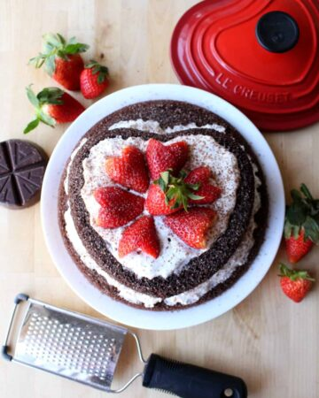 Mexican Chocolate Cake decorated with red heart-shaped strawberries.