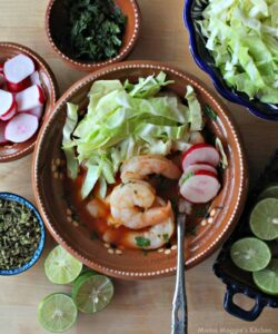 Shrimp Pozole in a clay bowl surrounded by the toppings for the stew.