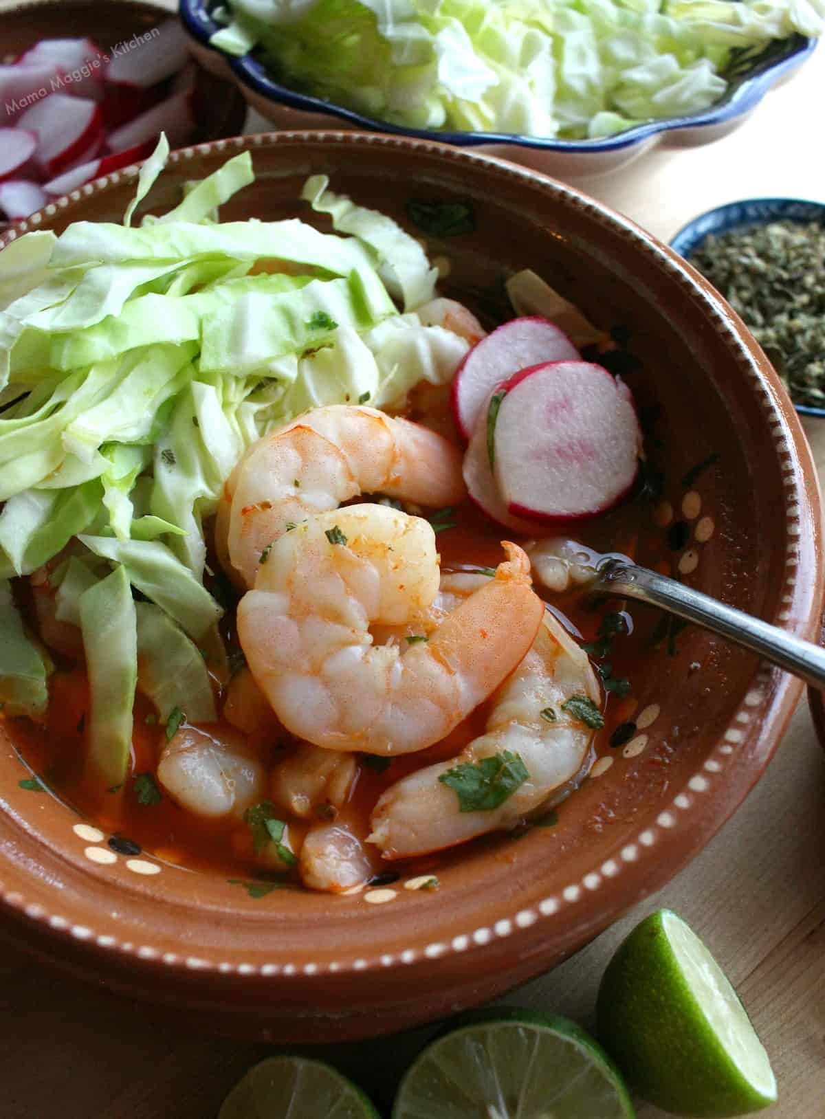 Shrimp Pozole (Pozole de Camaron) in a clay bowl with toppings.