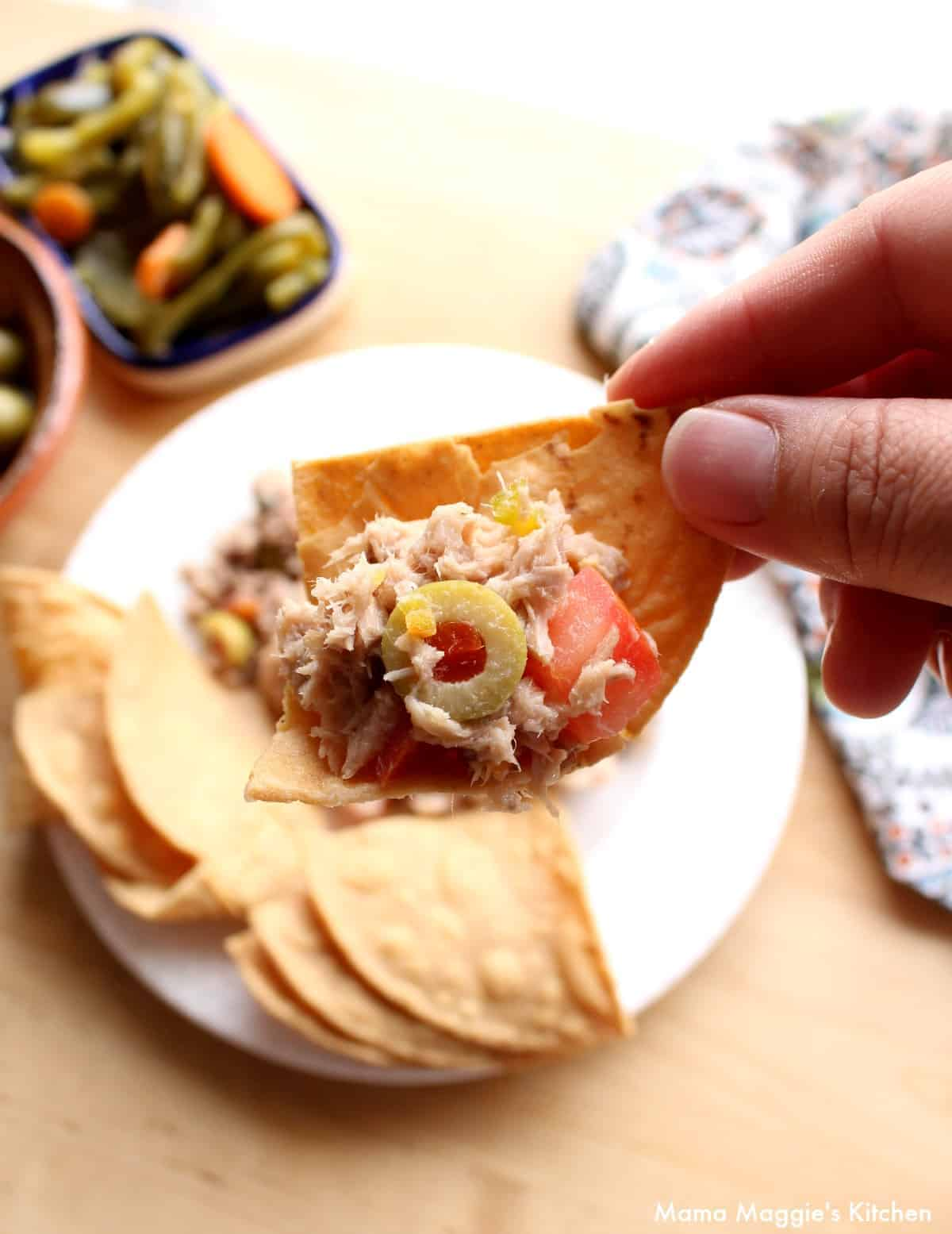 A hand holding a chip with Atun a la Veracruzana on it.