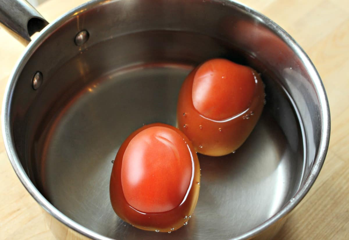 Two tomatoes covered with water in a sauce pan.