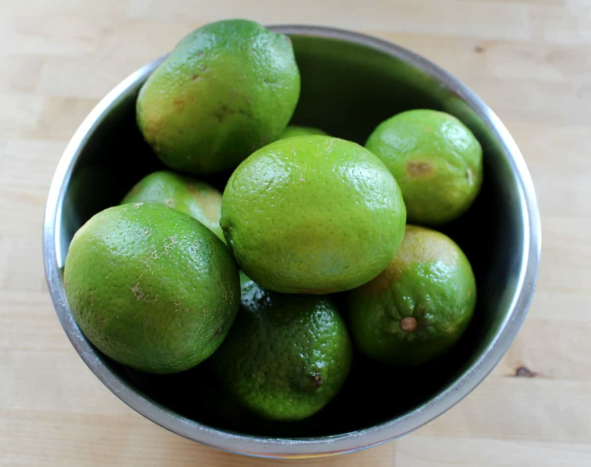A metal bowl with green limes inside.