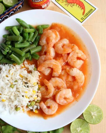 Camarones Enchipotlados surrounded by green beans and white rice next to lime wedges and a can of chipotle.