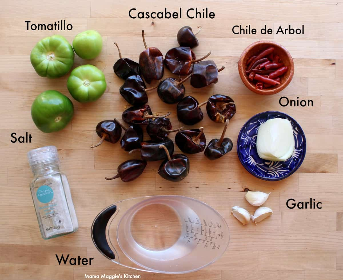 Ingredients for cascabel salsa on a wooden surface.