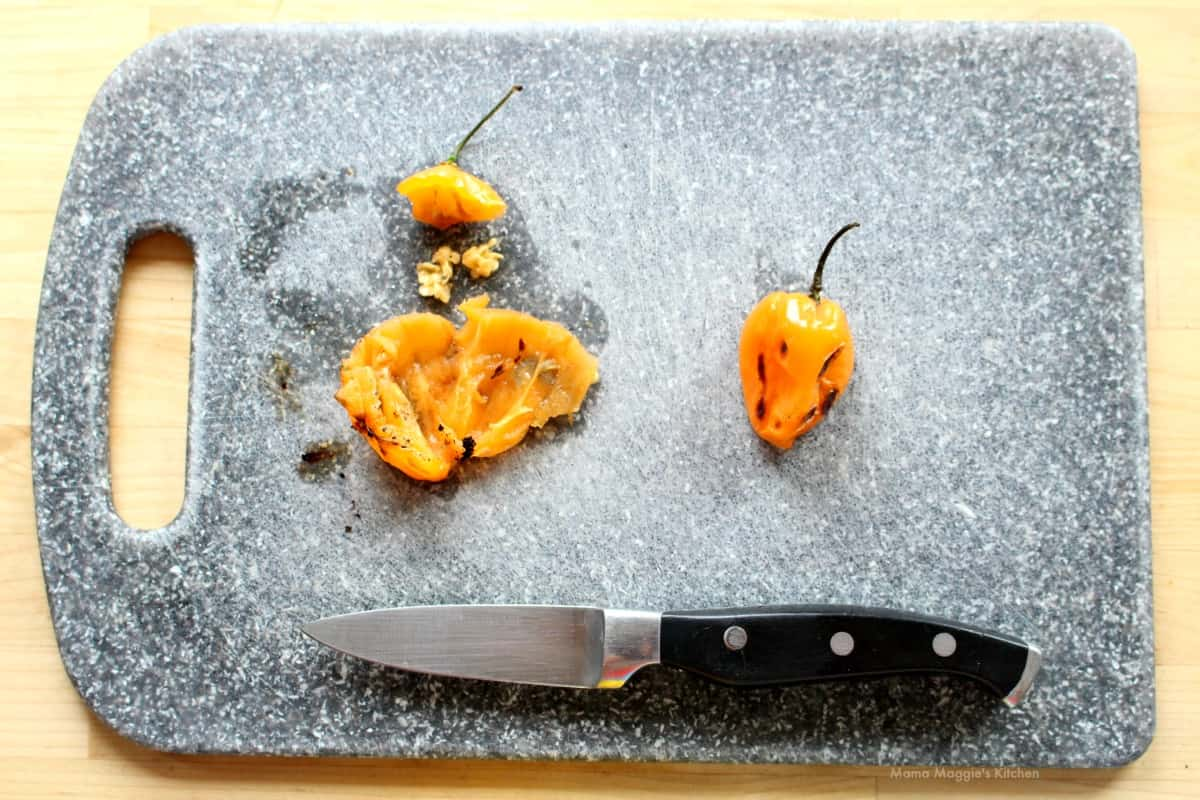 A picture showing how to remove the seeds and stem of a roasted habanero.