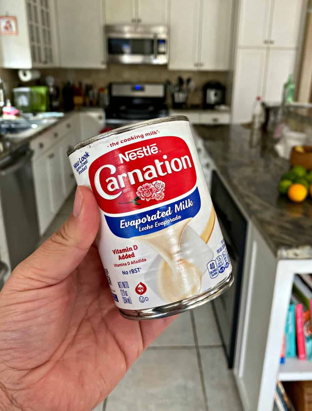A hand holding a can of Carnation Evaporated Milk in a kitchen.