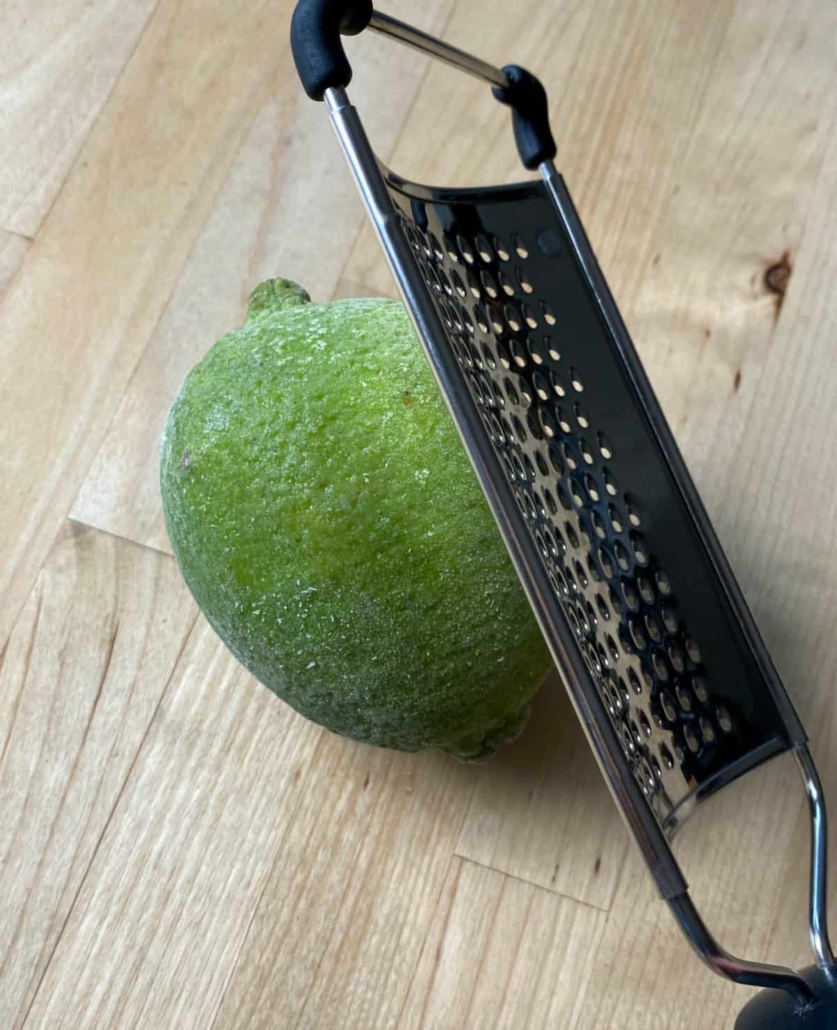A grater grating the zest of a frozen lime.