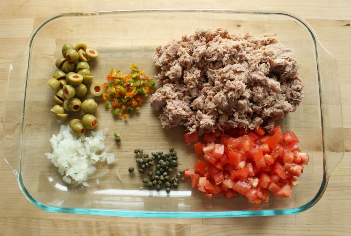 All the ingredients for Atun a la Veracruzana in a large glass baking dish.