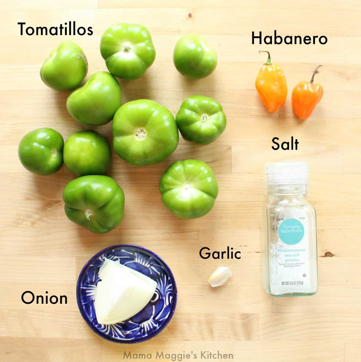 The ingredients necessary to make Tomatillo Habanero Salsa on a wooden table.