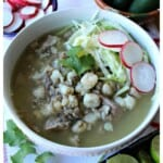 Instant Pot Pork Pozole Verde in a white bowl topped with cilantro, radishes, and cabbage.