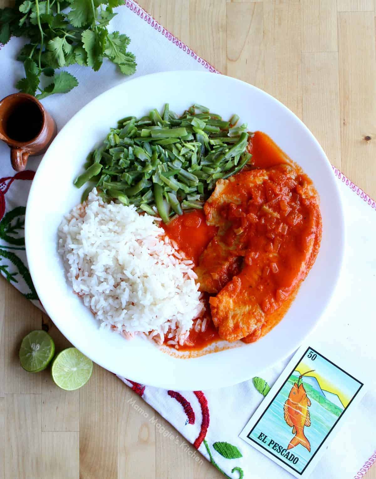 Pescado a la Diabla served on a plate with rice and green beans next to lime and cilantro.