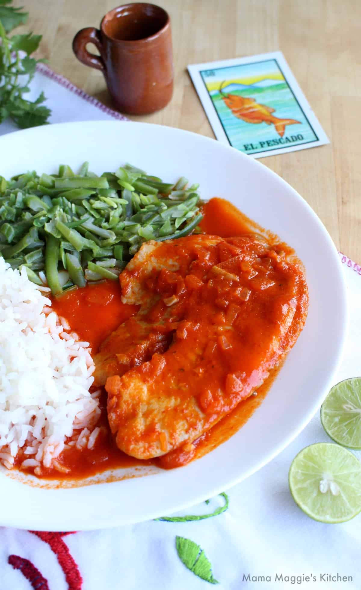 Deviled Fish served on a white plate next to white rice and green beans.