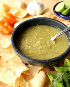 Tomatillo Habanero Salsa in a black bowl surrounded by chips.