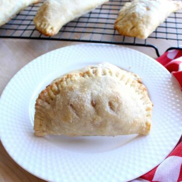 An apple empanada on a white plate next to a red checkered napkin and more empanadas cooling.